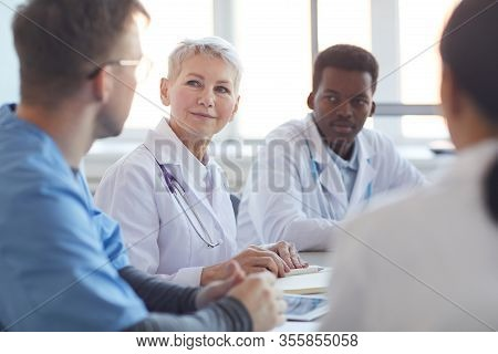 Multi Ethnic Group Of Doctors Sitting At Table, Focus On Mature Woman Heading Committee Meeting At M