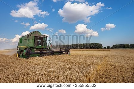Dobrich, Bulgaria - July 13: Modern John Deere Combine Harvesting Grain In The Field Near The Town D