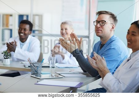 Multi-ethnic Group Of Doctors Applauding While Sitting At Table During Medical Conference, Focus On