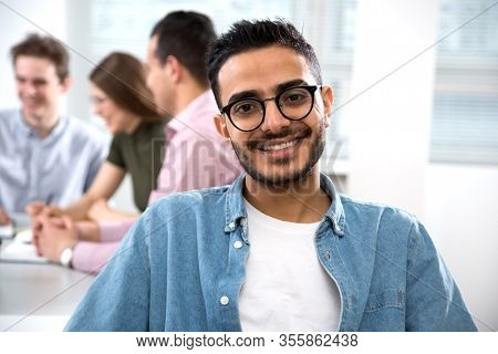Portrait of a happy arab student against the background of his friends in class