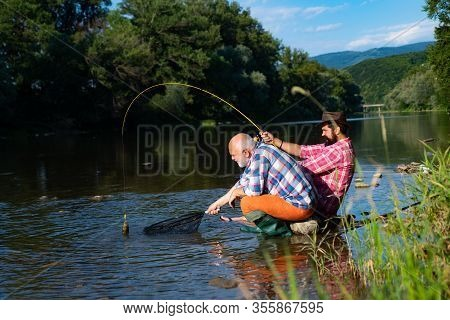 Men Fishing Relaxing While Enjoying Hobby. Fishing Freshwater Lake Pond River. Fishermen In Hats. Tw