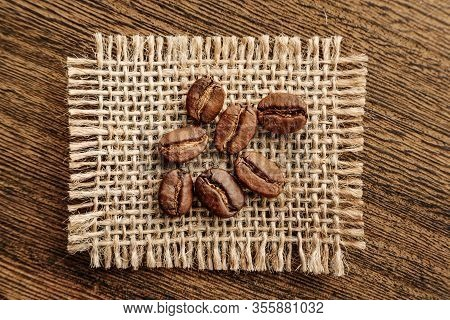 Coffee Beans On A Burlap Flap Close-up On A Background Of Rough Wood.