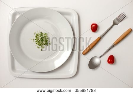 Two Red Cherry Tomatoes Between A Fork And A Spoon, Small Bunch Of Green Watercress On A Round White