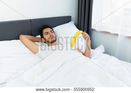 A Young Guy Is Lying In Bed With A Banana. Conceptual Photo About Erection Problems.
