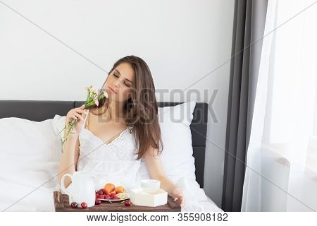 A Young Attractive Girl With Long Hair Is Sitting In A White Peignoir On The Bed. A Woman Is Enjoyin
