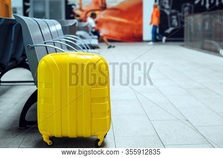 Vacation And Travel. Yellow Suitcase In The Waiting Room. Copy Space. Concept Waiting For The Plane.