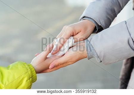 People Disinfecting Hands With Antiseptic Wet Wipe Outdoors. Antiseptic Napkin To Prevent Spread Of