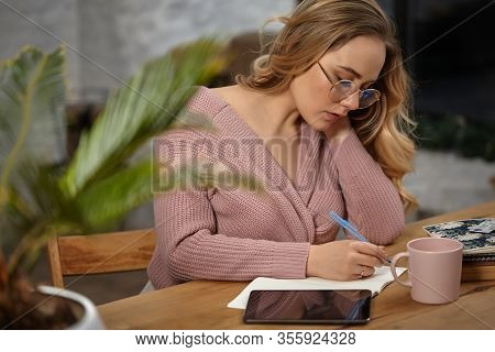 Girl In Glasses, Pink Cardigan. Holding Pen, Sitting At Wooden Table With A Tablet, Notebook, Cup An