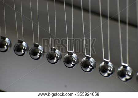 Business Concept For Strategy Team Work And Alignment. Newtons Cradle Pendulum.