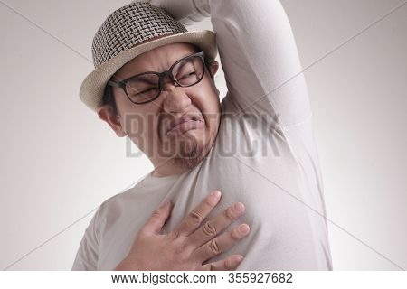 Portrait Of Funny Young Asian Man Smelling His Own Body, Bad Body Odor Problem