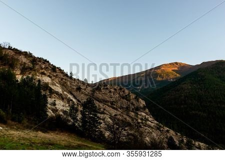 A Mountain Range Illuminated By Warm Sunlight During The Early Sunset (french Alps)