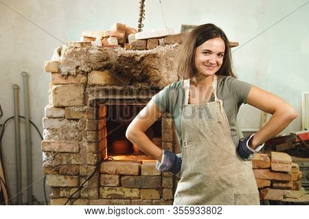 Potter Girl Smiling In Workshop On Background Of Brick Oven. Female Mastery Concept.