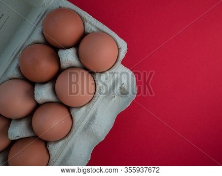 Overhead View Of Brown Chicken Eggs In An Open Egg Carton Isolated On Red. Fresh Chicken Eggs Backgr