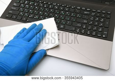 Disinfection In Public Places, The Fight Against The Virus, Coronavirus. A Working Hand Wipes A Lapt