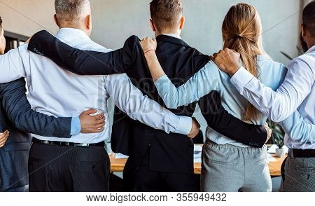 Teambuilding Concept. Unrecognizable Coworkers Standing Back To Camera Embracing During Corporate Me