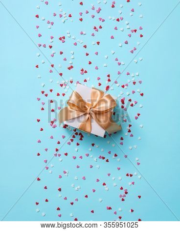 Gift box with golden tied bow, among tiny heart shapes. Top view holiday background.