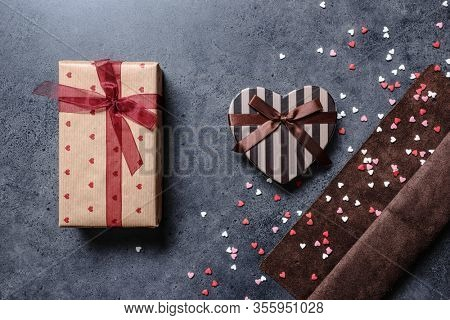 Holiday background of two gift boxes with scattered hearts around. Top view.