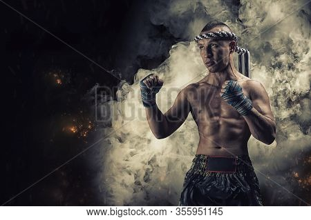Portrait Of A Boxer Of Mixed Martial Arts Standing On The Background Of Smoke And Fire. The Concept