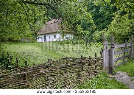 Ancient Peasant Ukrainian House In The Spring With A Thatched Roof In The Old Village Of National Ar