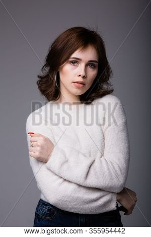 Beautiful Spanish Girl In A Light Sweater Looks Seriously And Incredulously, Hugging Herself
