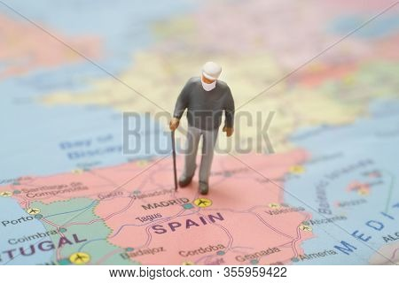 Figurine Of An Elderly Man Wearing Medical Mask On A Map Of Spain.