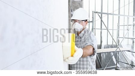 Man Builder Using A Sponge On  Wall Professional Construction Worker With Mask, Safety Hard Hat, Glo
