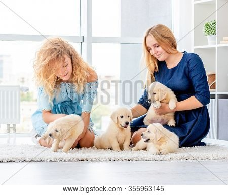 Happy girls playing with golden retriever puppies in light room