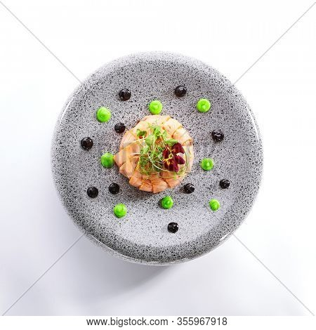 Salmon olivier salad with sauces. Sliced fish dish with greenery. Tasty seafood decorated with violet flower. Haute cuisine on plate. Restaurant meal, elegant food composition