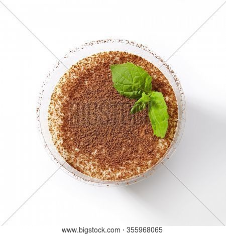 Gourmet Italian tiramisu dessert in restaurant glass decorated with fresh mint and cocoa powder isolated on white. Coffee flavored sweet cream mousse or cacao pudding closeup