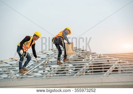 Construction Worker Wearing Safety Harness Belt During Working On Roof Structure Of Building On Cons