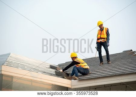 Roofer Worker In Protective Uniform Wear And Gloves,using Air Or Pneumatic Nail Gun And Installing C