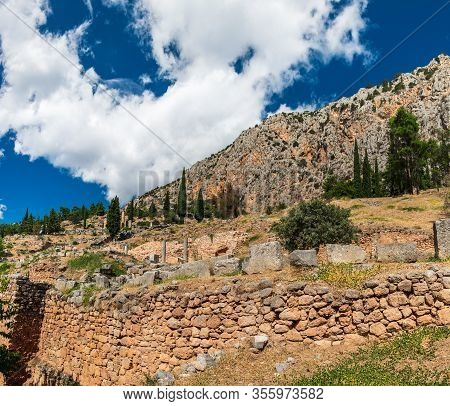Greek Temple Of Apollo In Archaeological Site Of Delphi, Central Greece. Summer Scenic Landscape Wit