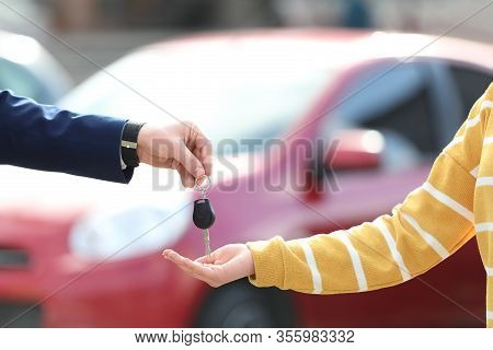Salesman Giving Key To Customer In Modern Auto Dealership, Closeup. Buying New Car