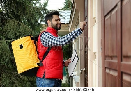 Courier With Thermo Bag And Clipboard Knocking On Customer's House. Food Delivery Service