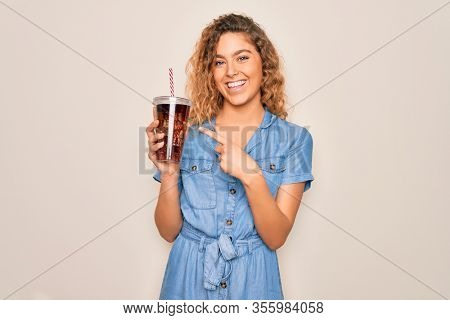 Beautiful blonde woman with blue eyes drinking cola beverage using straw to refreshment very happy pointing with hand and finger