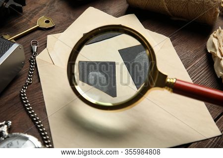 Magnifying Glass  And Fingerprints On Wooden Table, Closeup. Detective's Workplace