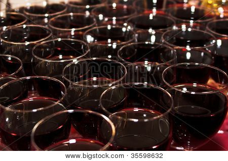 A bunch of glasses with red wine. Close-up shot.