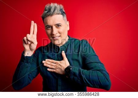 Young handsome modern man wearing elegant green shirt over red isolated background smiling swearing with hand on chest and fingers up, making a loyalty promise oath