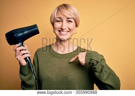 Young blonde woman with short hair drying her hair using hairdryer over yellow background with surprise face pointing finger to himself