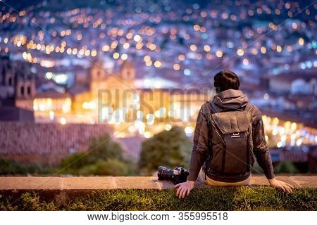 Asian Man Traveler And Photograpaher Sitting On Viewpoint Looking At Illuminated Cusco City At Night