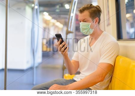 Young Man Using Phone Inside The Train With Mask For Protection From Corona Virus Outbreak