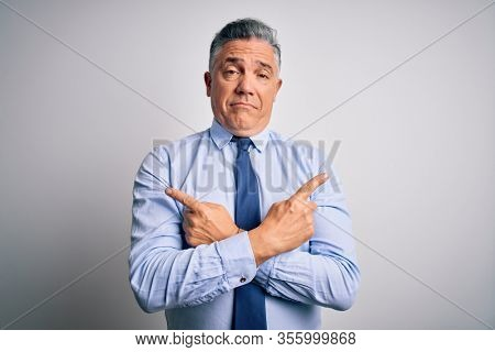 Middle age handsome grey-haired business man wearing elegant shirt and tie Pointing to both sides with fingers, different direction disagree