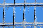 Closeup of ice built up on wire fence in winter against blue sky poster