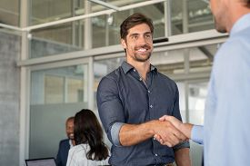 Two cheerful businessmen shaking hands after an agreement. Two confident business men shaking hands and smiling while standing in modern office with copy space. Handshake for greeting and dealing.