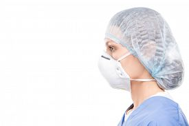 Side view of female medical specialist in protective mask and surgical cap against white background