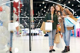 Cheerful young women with shopping bags standing at display case and choosing clothes in mall