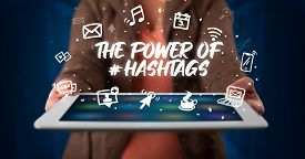 Young business person working on tablet and shows the inscription: THE POWER OF #HASHTAGS