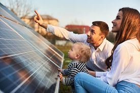 Man Shows His Family The Solar Panels On The Plot Near The House During A Warm Day. Young Woman With