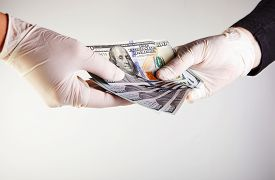 The Hand Of A Man In A White Medical Glove Gives Money To A Woman In A White Medical Glove In The Fo