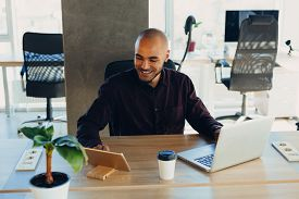 Smiling Bearded African Man Using Laptop At Home, Sitting On A Wooden Table. Concept Of Young People